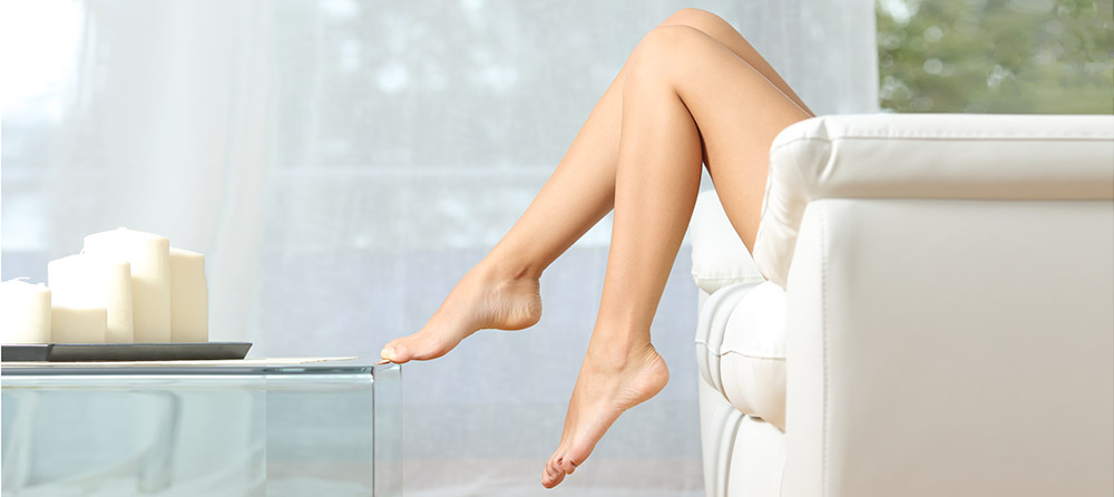 Profile of a perfect woman legs sitting on a couch at home hair removal concept